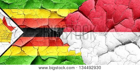 Zimbabwe flag with Indonesia flag on a grunge cracked wall