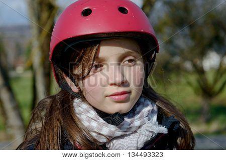 a preteen girl wearing a roller skate helmet.