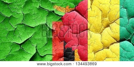 Zambia flag with Guinea flag on a grunge cracked wall