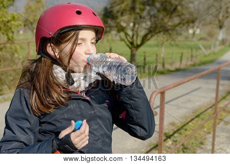 a preteen with roller skate helmet drink a water
