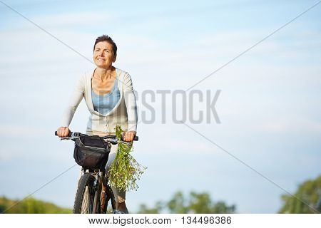 Old smiling woman cycling with her bike in summer