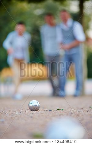 Metal ball of boule game laying in sand