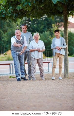 Senior group playing boule together in summer in city