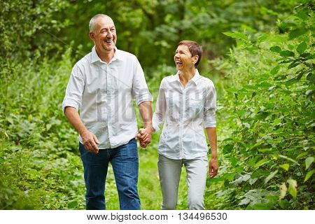 Happy senior couple taking a walk in a forest in summer