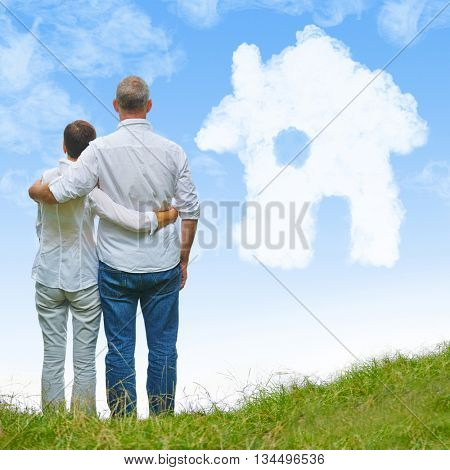 Senior couple looking to white dream house made of clouds in a blue sky