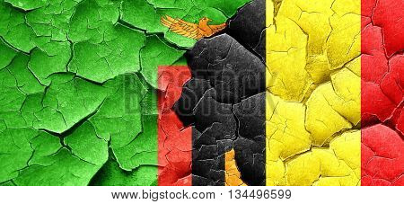 Zambia flag with Belgium flag on a grunge cracked wall