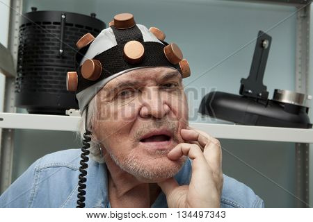 Aged man crazy inventor wearing a helmet brain research