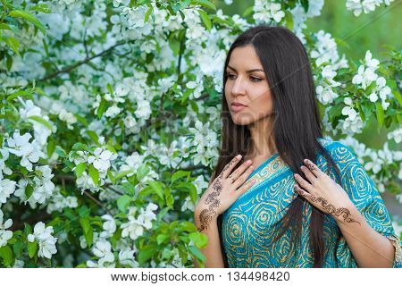Asian woman near blooming apple tree with henna tattoo