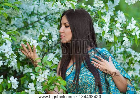 Asian woman with henna tattoo in flowering bushes