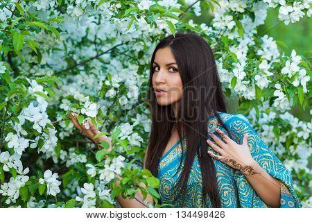 Beautiful woman with henna tattoo near blooming apple tree