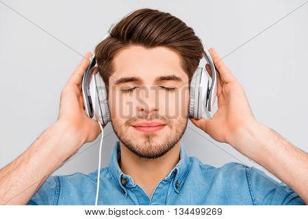 Stylish Happy Man Listening To Music On White Headphones