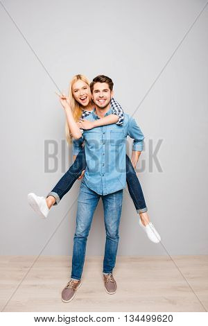 Happy Cheerful Man Carrying His Smiling Girlfriend On The Back