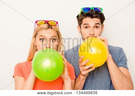Portrait Of Attractive Man And Woman In Glasses Inflating Balloons