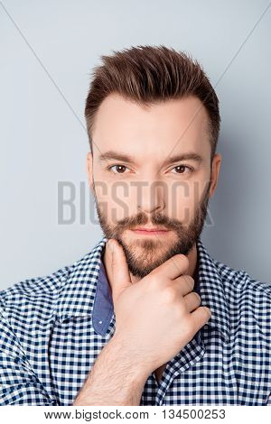 Portrait Of Young Minded Man Touching His Chin