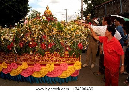 SARABURI, THAILAND - JUL 22 2005 : Group of people give a  flower for offering in Tak Bat Dok Mai or Flower Offering Ceremonyof Wat Phra Buddhabat Woramahaviharn temple in Saraburi,Thailand.
