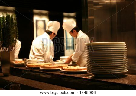 two chefs working in a busy restaurant kitchen