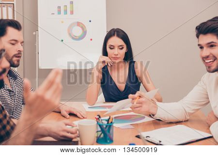 young beautiful businesswoman sitting at the conference near flipchart and thinking