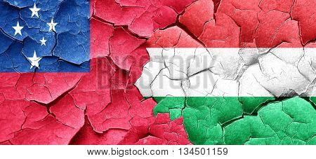 Samoa flag with Hungary flag on a grunge cracked wall