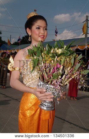 SARABURI THAILAND - JULY 20,2005 : Pretty woman on traditional dress holding flower on parade in Tak Bat Dok Mai Festival is Ceremony of Wat Phra Buddhabat Woramahaviharn temple in Saraburi Province,Middle of Thailand.