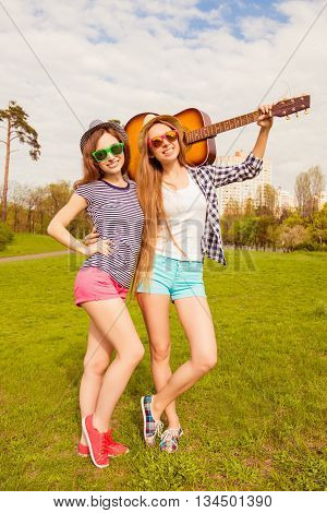 Pretty Sexy Girls In Hats And Glasses Walking In Park With Guitar