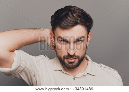Handsome Serious Young Man Combing His Hair With Fingers