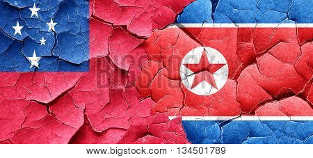 Samoa flag with North Korea flag on a grunge cracked wall