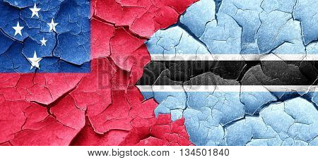 Samoa flag with Botswana flag on a grunge cracked wall