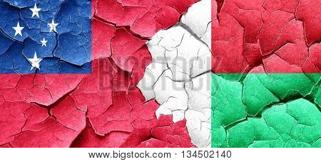 Samoa flag with Madagascar flag on a grunge cracked wall