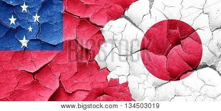 Samoa flag with Japan flag on a grunge cracked wall