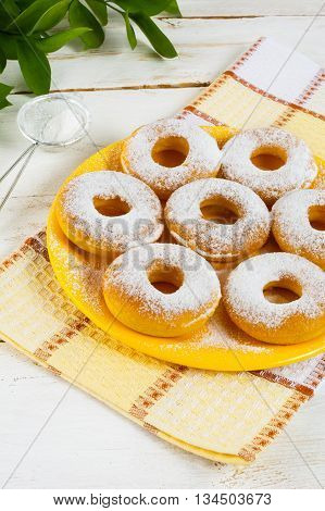 Caster sugar powdered donuts on yellow plate. Sweet dessert. Sweet pastry doughnuts. Hanukkah homemade donuts.