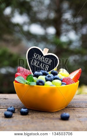 Fresh Organic Fruits On Wooden Table, Heart With German Text