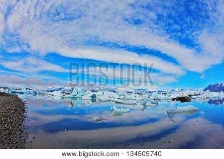 Yokulsarlon Glacial Lagoon in Iceland. Cirrus clouds are beautifully reflected in the smooth water of the ocean lagoon