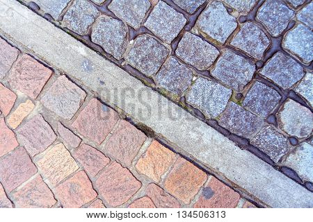 Cobblestone floor red and black divided by a strip of cement