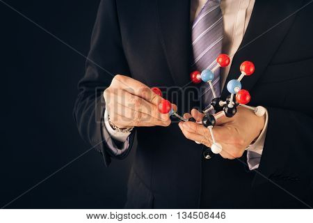 Businessman Assembling A Tnt Molecular Structure