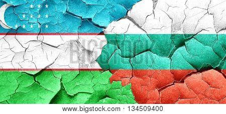 Uzbekistan flag with Bulgaria flag on a grunge cracked wall