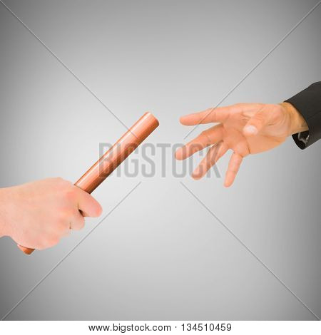 Athlete passing a baton to businessman on grey background