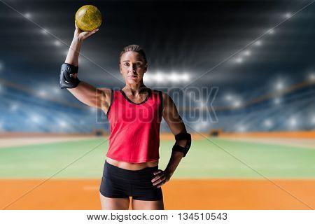Female athlete with elbow pad holding handball against handball field indoor