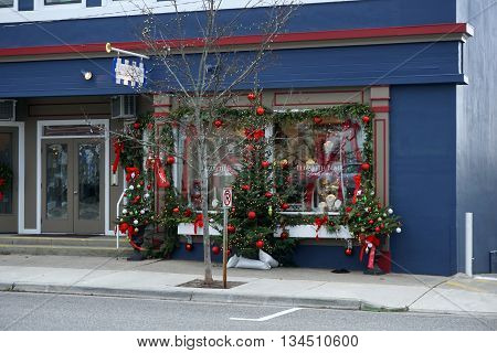 HARBOR SPRINGS, MICHIGAN / UNITED STATES - DECEMBER 24, 2015: Elizabeth Blair's Fine Pearls store is richly decorated for Christmas, with Christmas trees on the sidewalk in front of the store, on Main Street in downtown Harbor Springs.