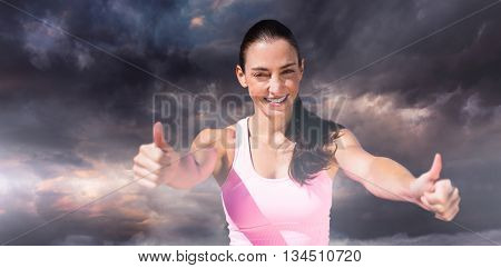 Portrait of sportswoman is smiling with thumbs up against gloomy sky