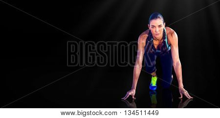 Composite image of sporty woman in the starting block against black background