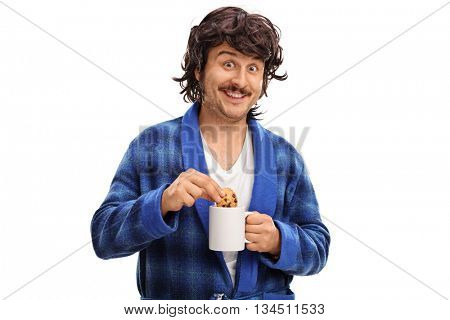 Man holding a cup of milk and dipping a chocolate chip cookie in it isolated on white background