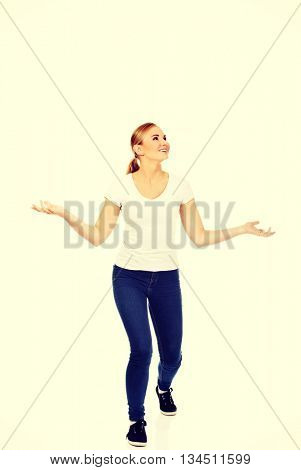 Young woman trying to catch something falling from the sky
