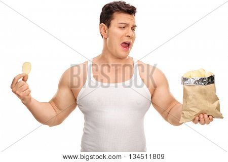 Displeased guy holding a bag of potato chips isolated on white background