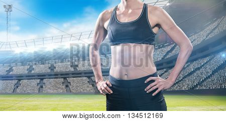 Female athlete standing with hand on hip against view of a stadium