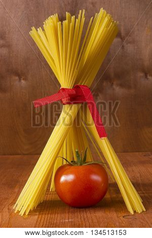 Tomato in a tent of spaghetti on a wooden background