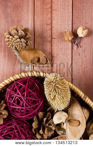 Colorful assorted potpourri in a wicker basket on a wooden table