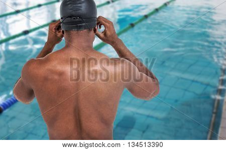 Rear view of swimmer in shirtless wearing swimming goggles against view of a swimming pool