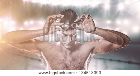 Swimmer holding swimming goggles against view of a swimming pool