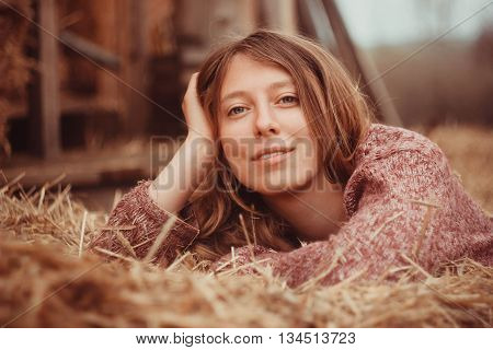 Cute country girl relaxed lying in hay.