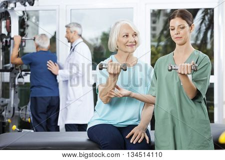 Nurse Instructing Senior Woman Exercising With Dumbbell
